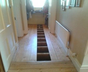 A typical suspended timber floor in an Edwardian hallway. Two floorboards have been lifted to expose the joists.